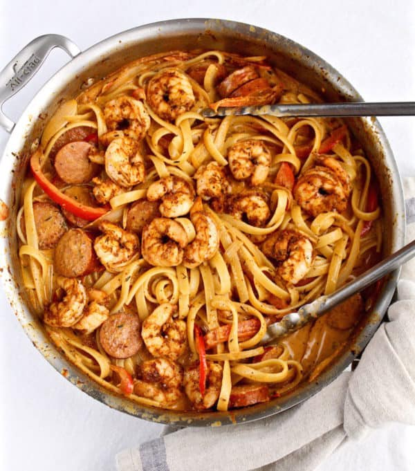 Creamy Cajun Shrimp Pasta in large skillet with tongs