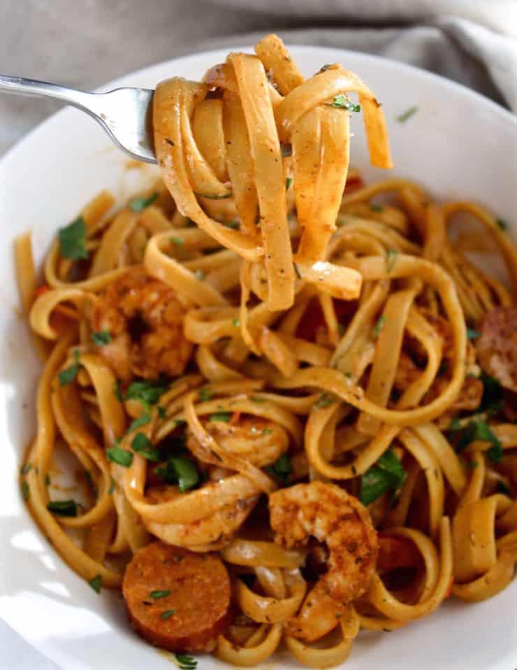 Creamy Cajun Shrimp Pasta with Sausage in bowl, forkful of pasta