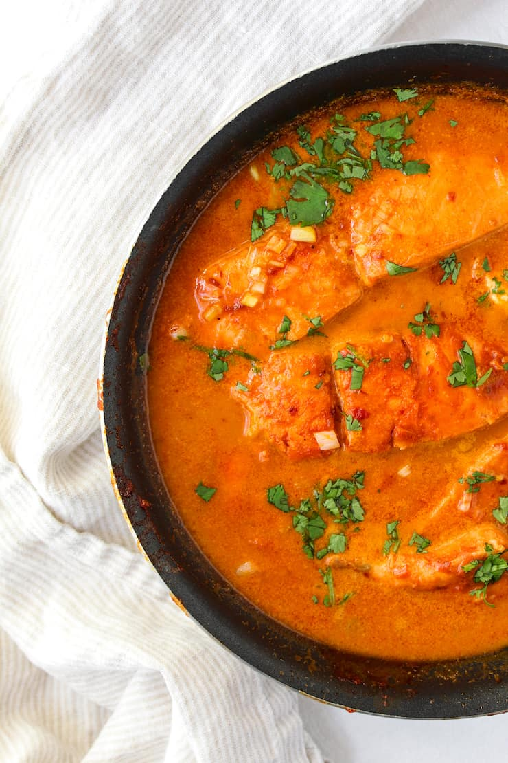 Salmon in coconut curry sauce in pan.