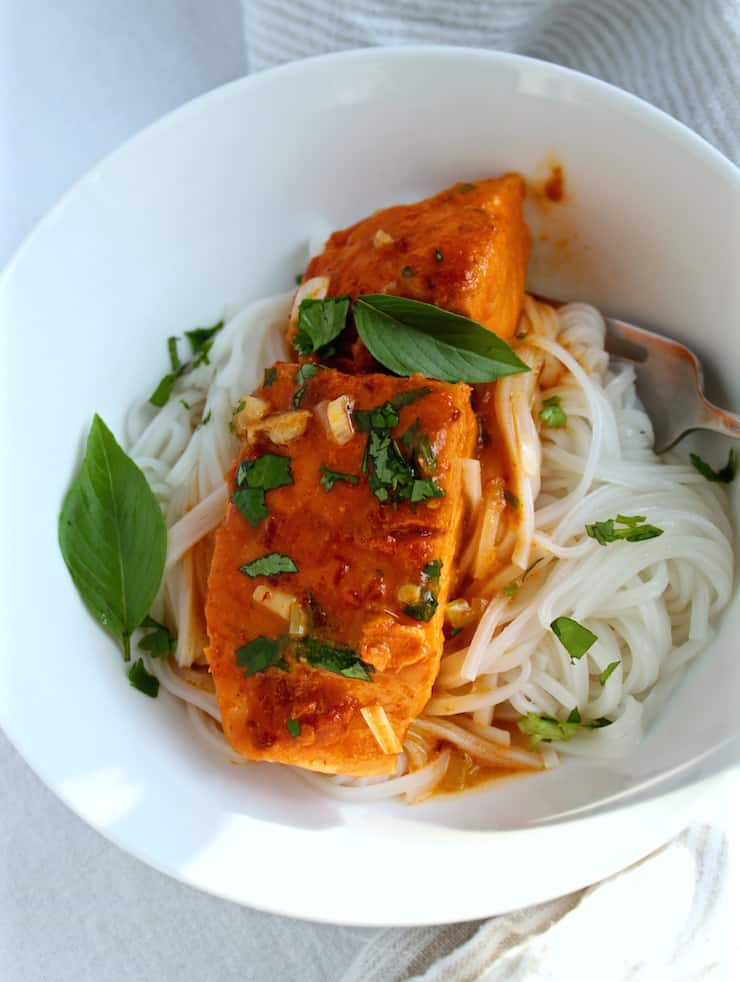Easy Coconut Curry Salmon, in serving bowl over rice noodles.