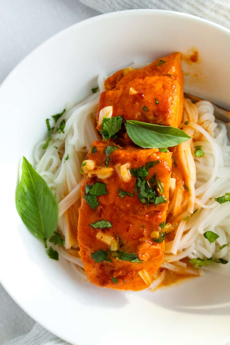 Plated coconut curry salmon over rice stick noodles.