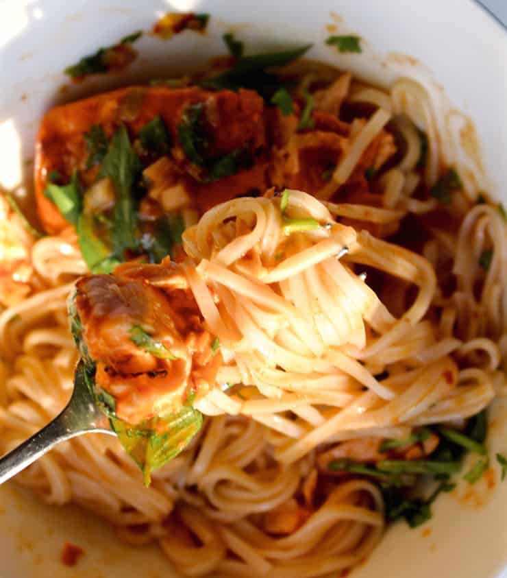 Easy Coconut Curry Salmon, on fork above bowl, swirled with rice noodles.