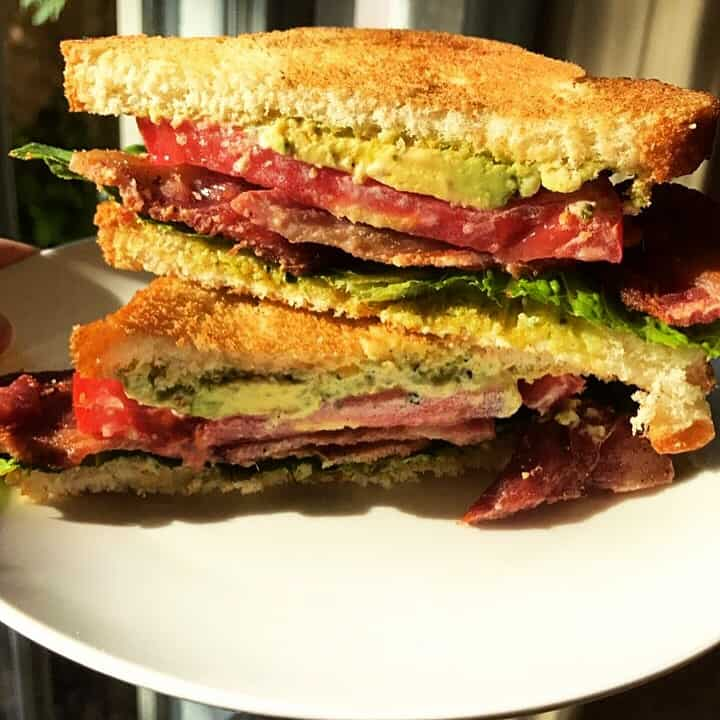 Stacked BLT sandwich with avocado and pesto mayo.