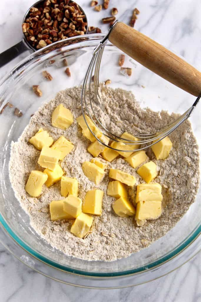 Cutting the butter into the dry ingredients with a pastry blender.
