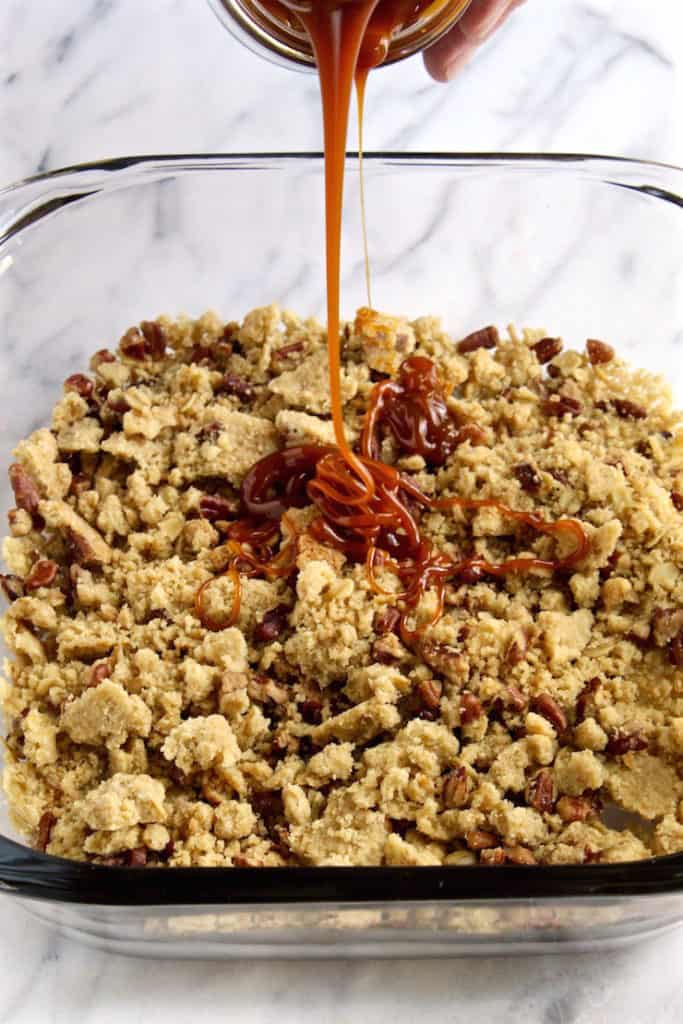 Drizzling caramel over the crumbles.