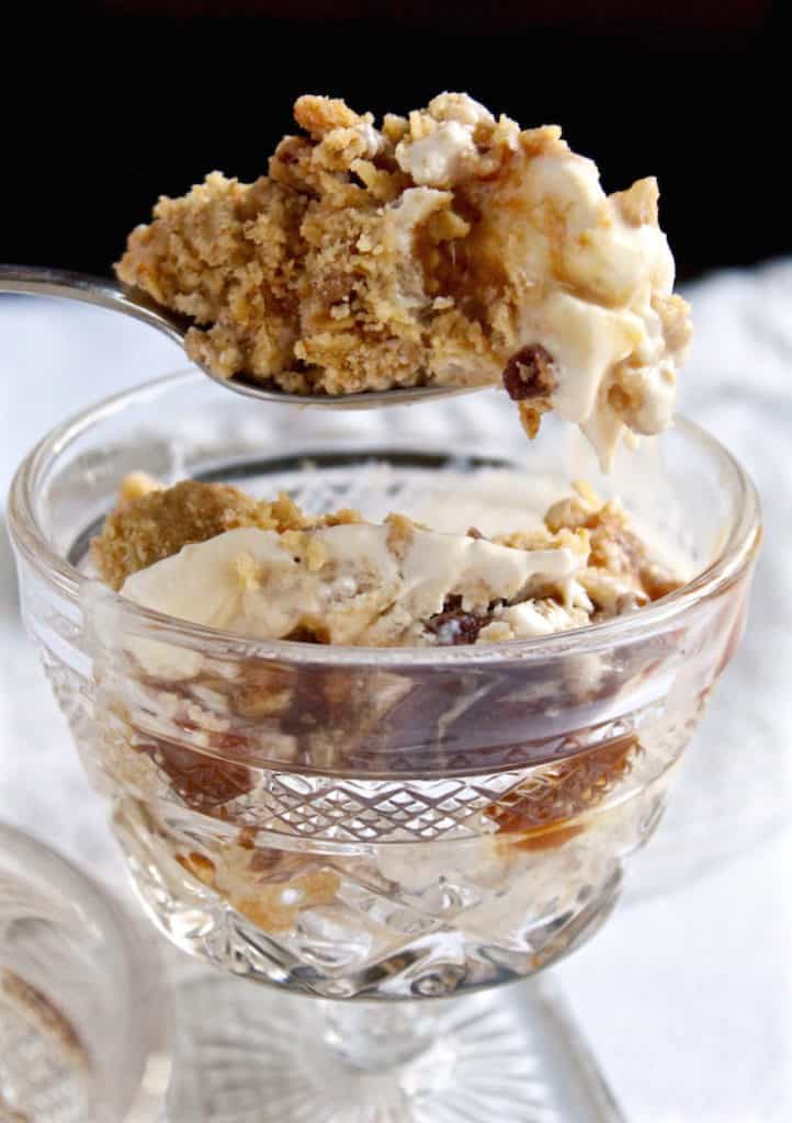 Spoonful of dessert above crystal serving dish.