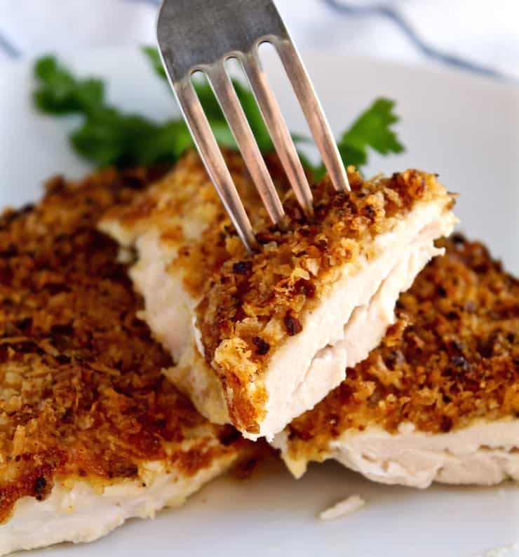 Crispy Onion Parmesan Chicken, cutting into chicken cutlet with fork.