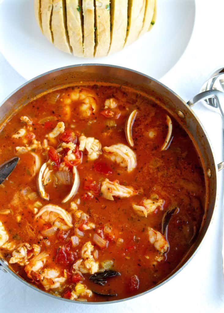 Pot of cioppino with sourdough bread in background