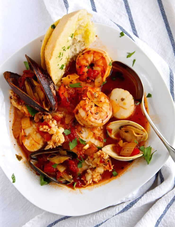 Cioppino in serving bowl with spoon and sourdough bread.
