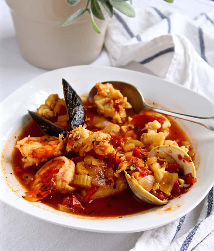 Classic Cioppino, in serving bowl with spoon showing all the seafood.