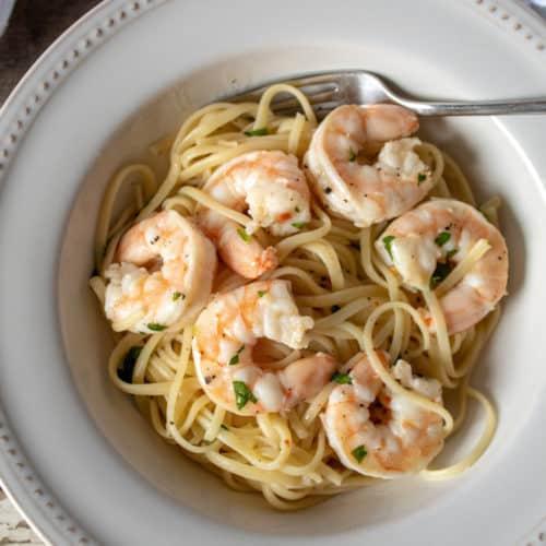 Shrimp Scampi, with linguine in serving bowl with fork.