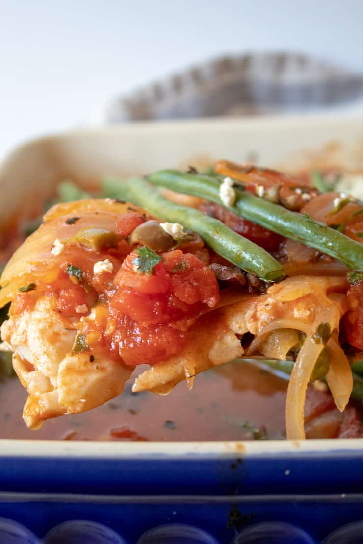 Mediterranean Baked Fish, close up on spatula with tomato mixture and green beans.