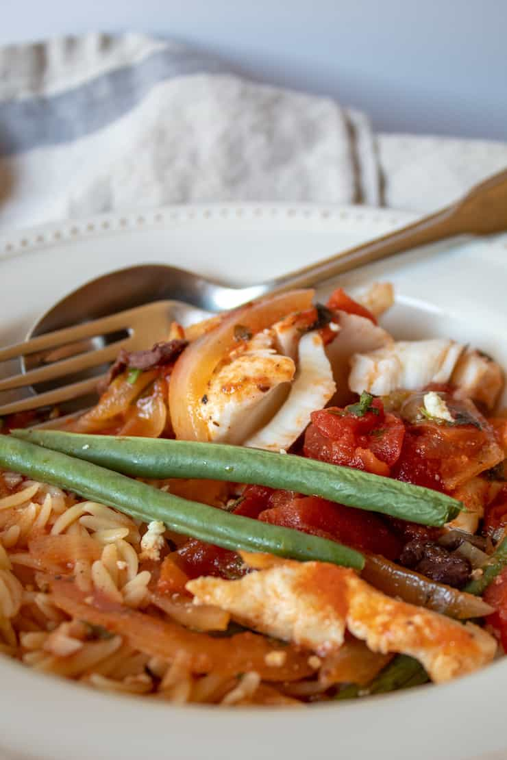 Mediterranean Baked Fish, in serving bowl with orzo pasta.