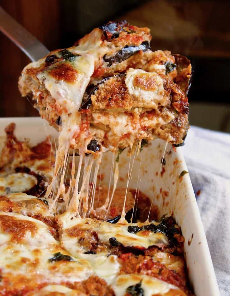 Eggplant Parmesan, serving piece with melty, gooey cheese out of baking dish