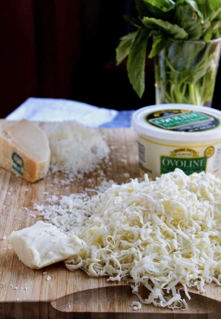 Shredded mozzarella, parmesan and fresh mozzarella on cutting board