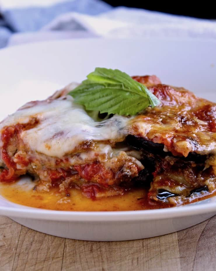 Eggplant Parmesan, serving of eggplant parmesan in dish with fresh basil