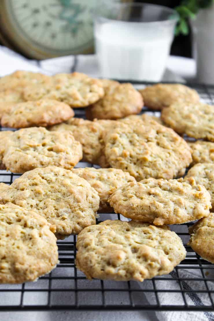 Oatmeal cookies on rack with glass of milk.