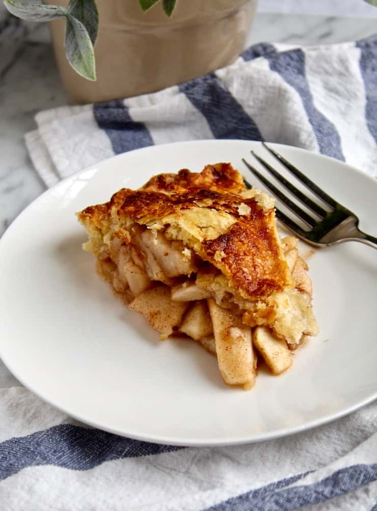 Slice of apple pie with fork on white plate.
