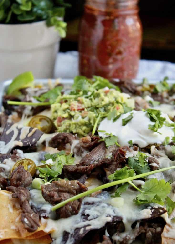 Loaded Steak Nachos in sheet pan with cilantro and jalapenos.