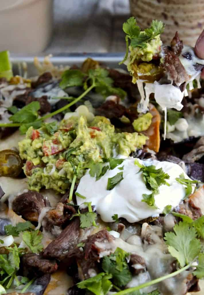 Loaded Steak Nachos, hand scooping up some nachos.