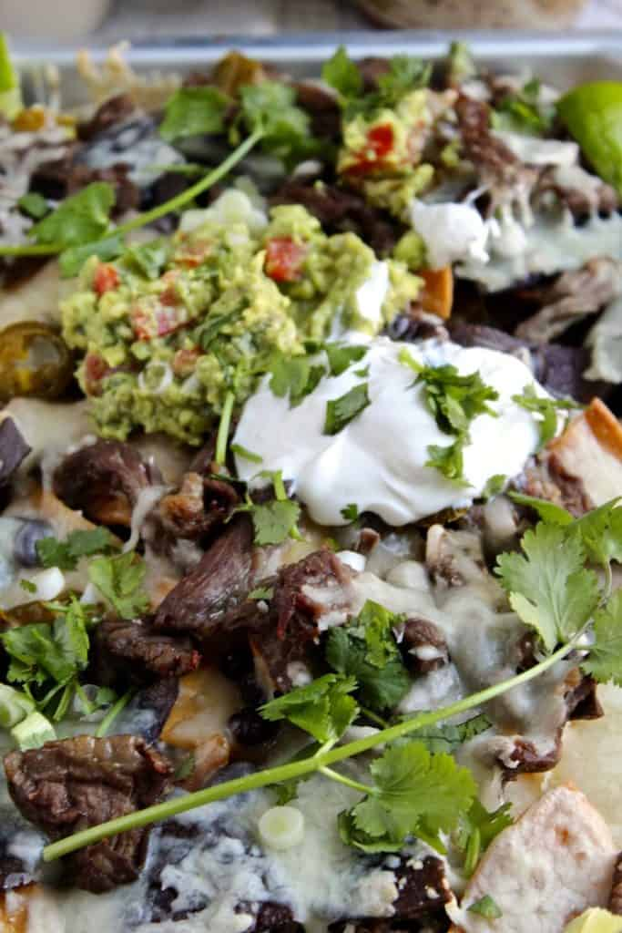 Close up of steak nachos and toppings in sheet pan.