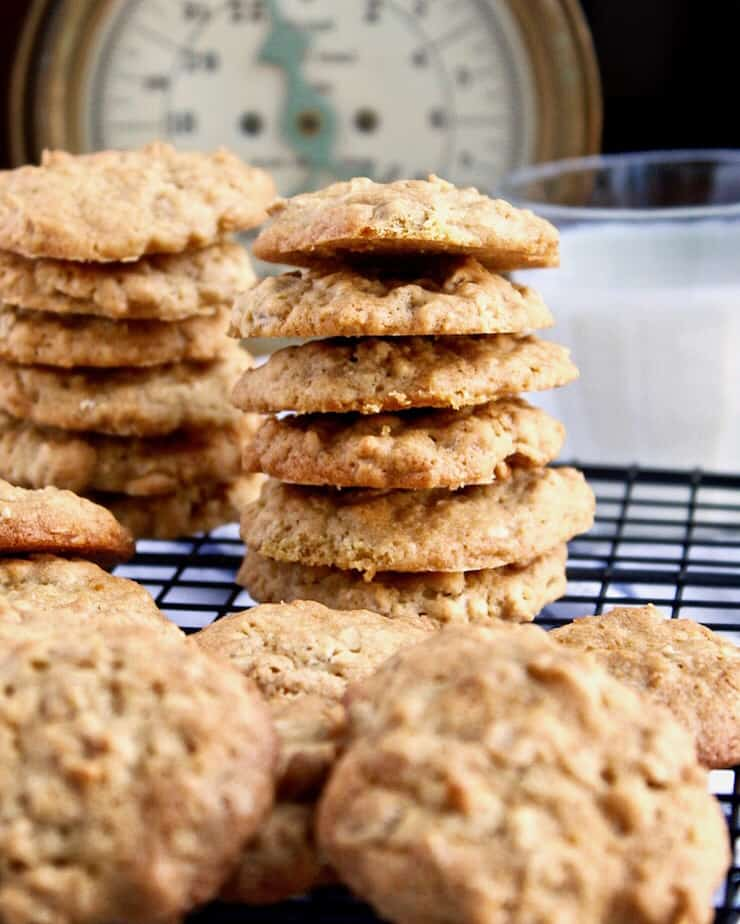 Old-Fashioned Oatmeal Cookies, stacked vertically on cooling rack with glass of milk