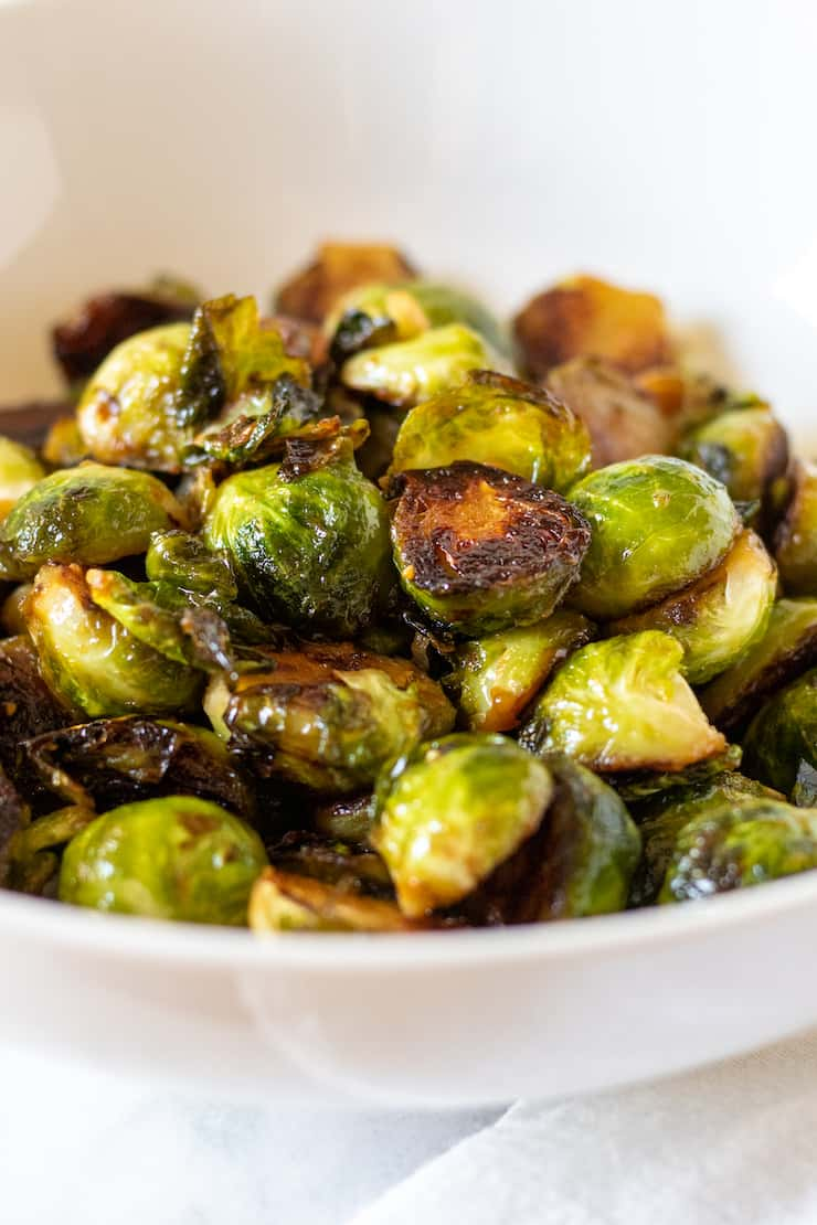 Caramelized stovetop Brussels sprouts in white serving bowl.