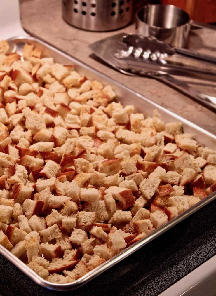 Old-Fashioned Bread Stuffing with Sausage, sheet pan of toasted bread cubes.