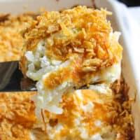 Cheesy potatoes close up on spatula above casserole dish.