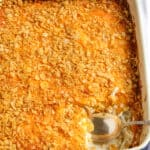Cheesy potatoes in casserole dish with spoon.