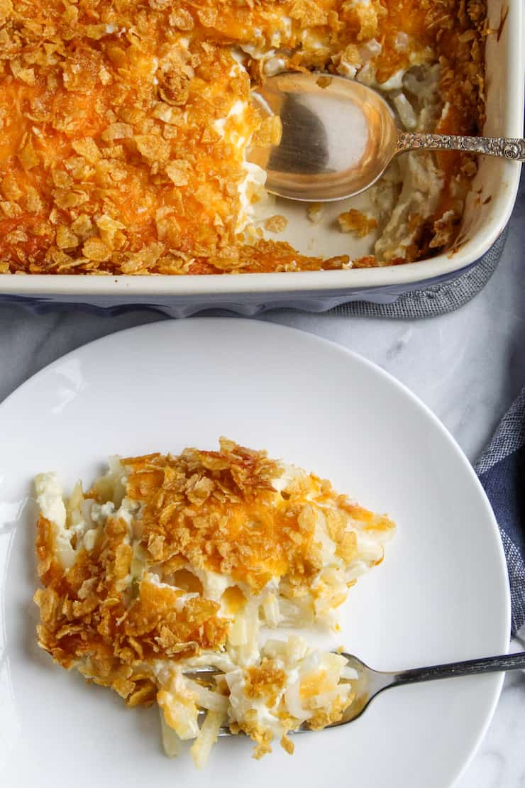 Cheesy potatoes casserole on white plate.