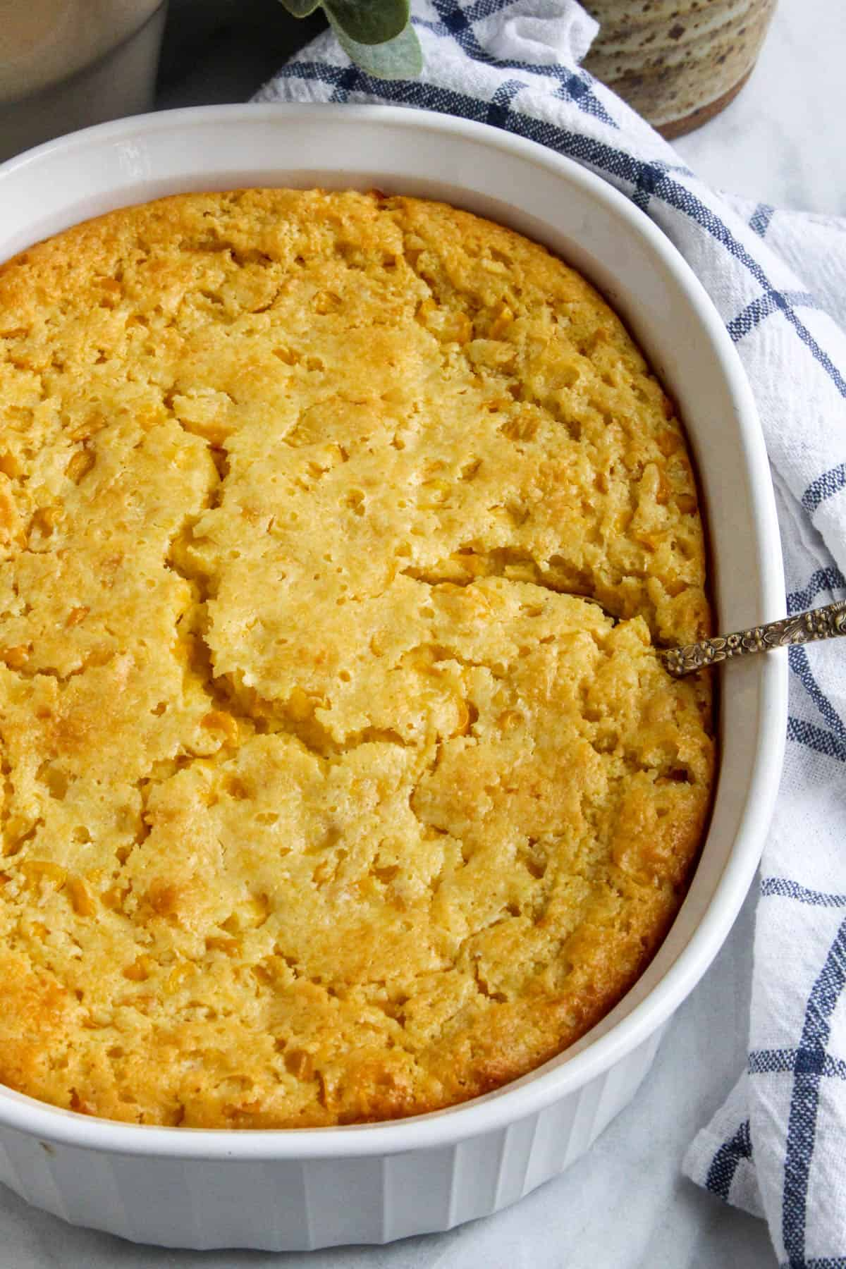 Overhead photo of baked corn soufflé in white casserole dish.