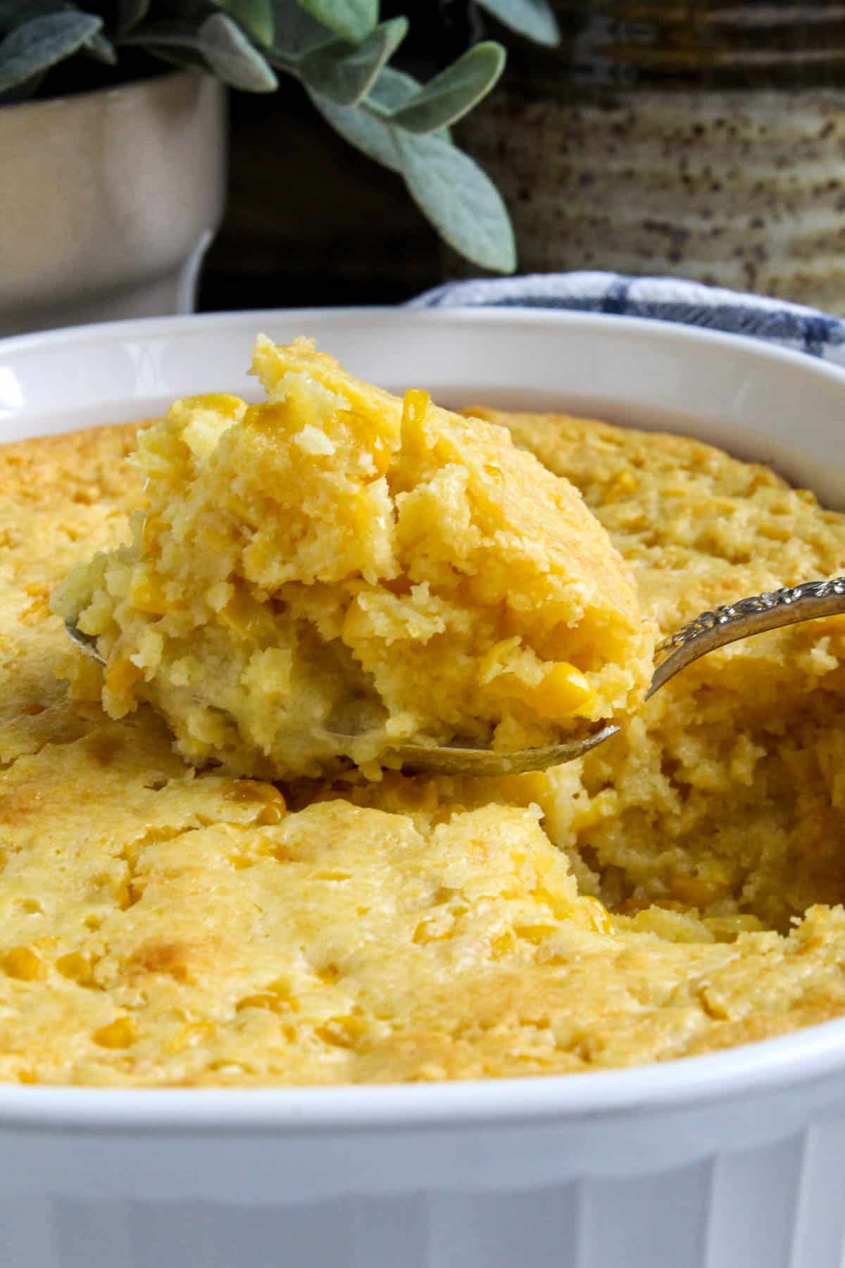 Close up of spoonful of corn soufflé coming out of casserole.