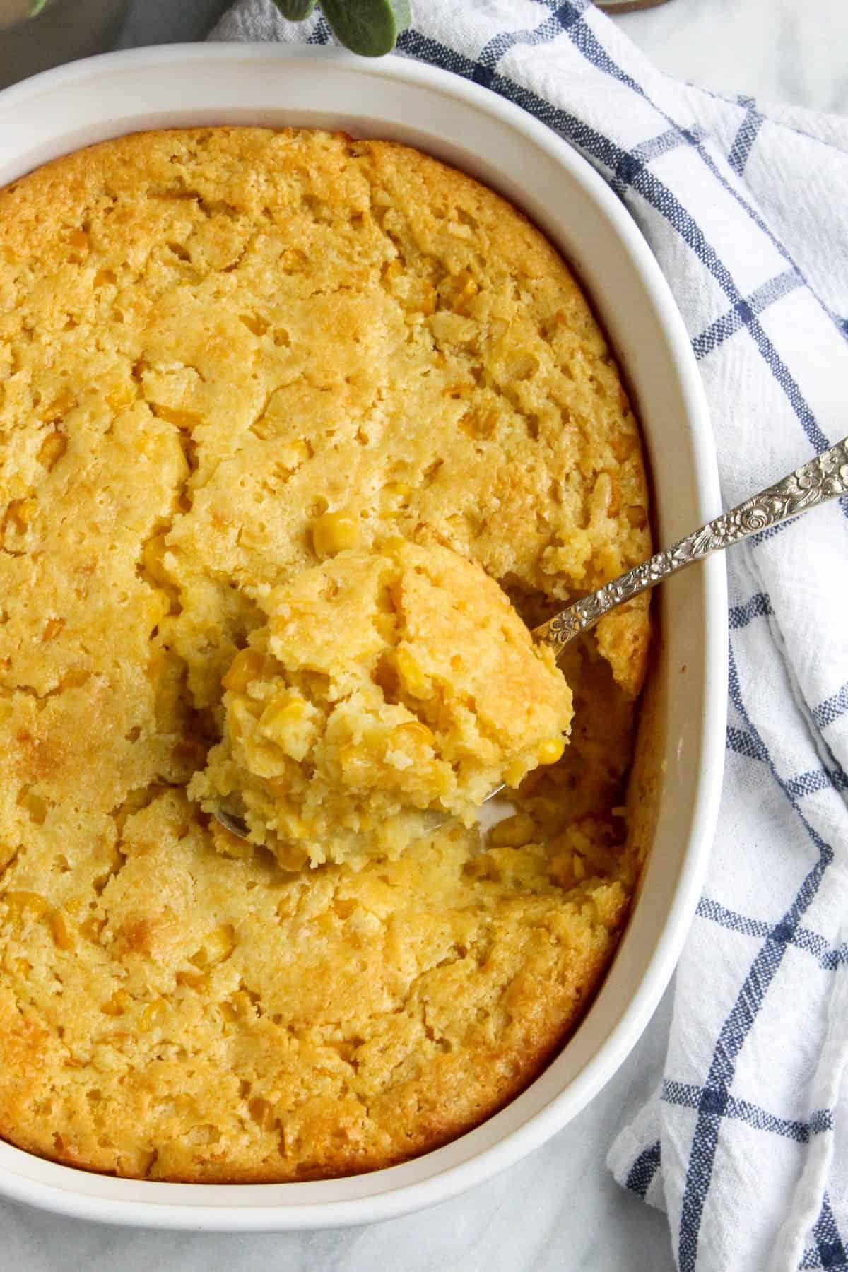 Overhead of corn soufflé with spoonful of corn casserole.
