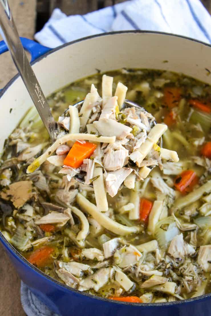 Pot of turkey noodle soup with ladle.