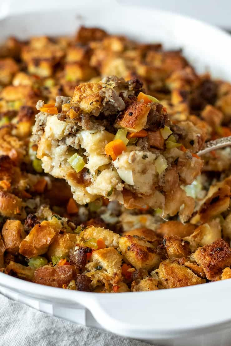 Spoonful of old fashioned bread stuffing in casserole dish.