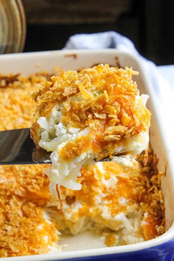 Cheesy potatoes on spatula above casserole.