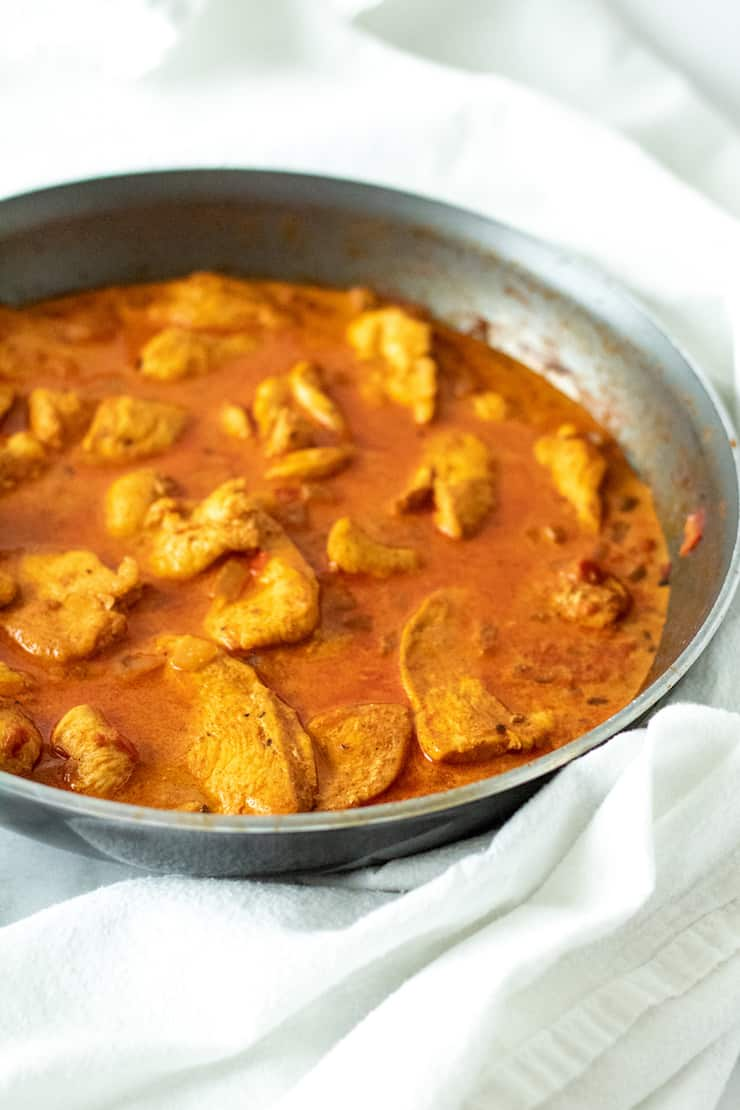 Side view of chicken paprikash in pan.