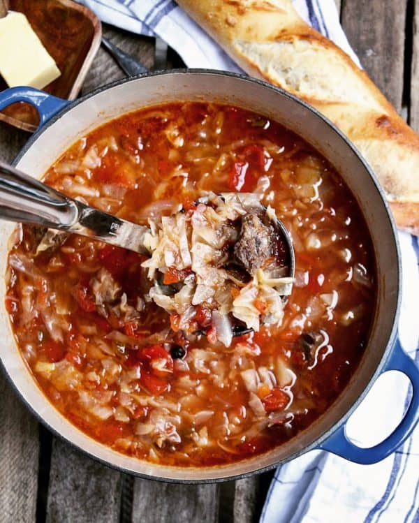 Sweet-and-Sour Beef Cabbage Soup, in soup pot with ladle full of soup.