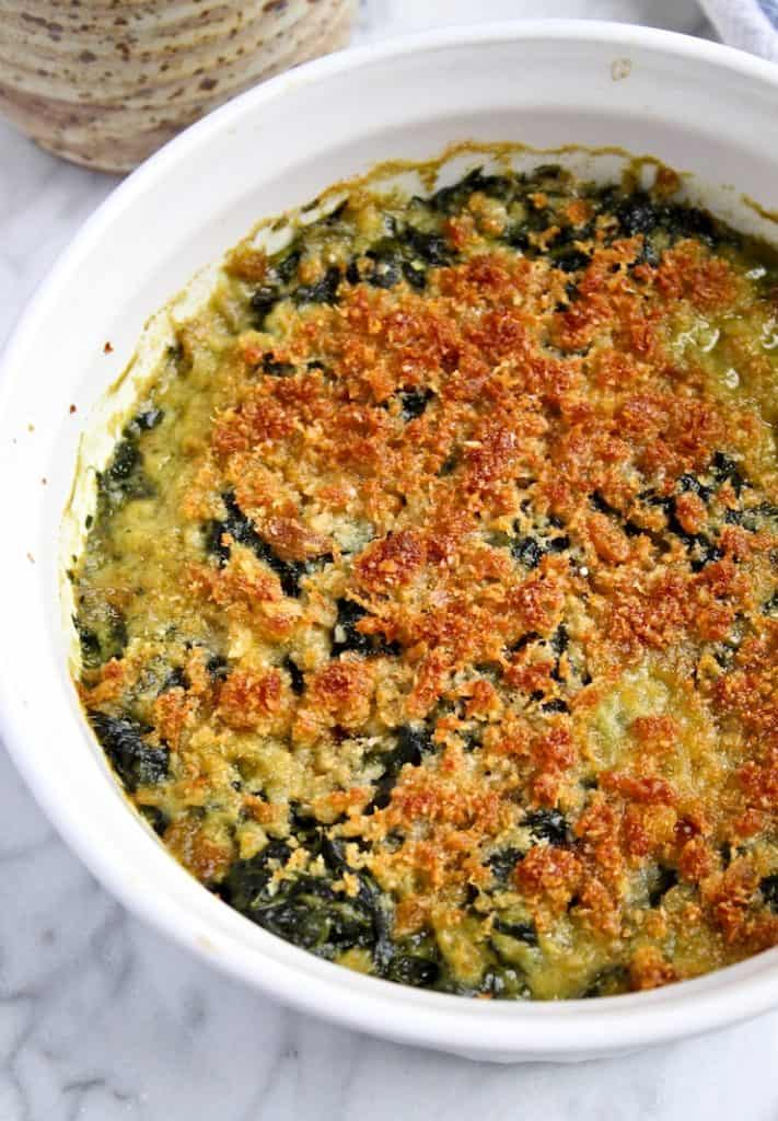 Browned topping over creamy spinach in casserole dish.