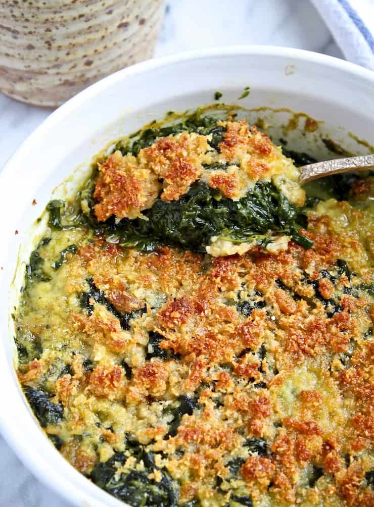 Spinach Rockefeller, casserole closeup with serving spoonful