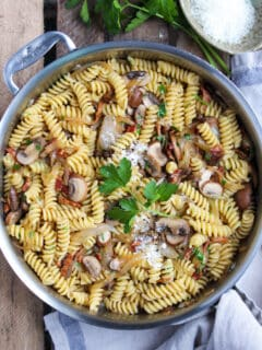 Pasta with bacon, onion and mushrooms in skillet with parmesan cheese.