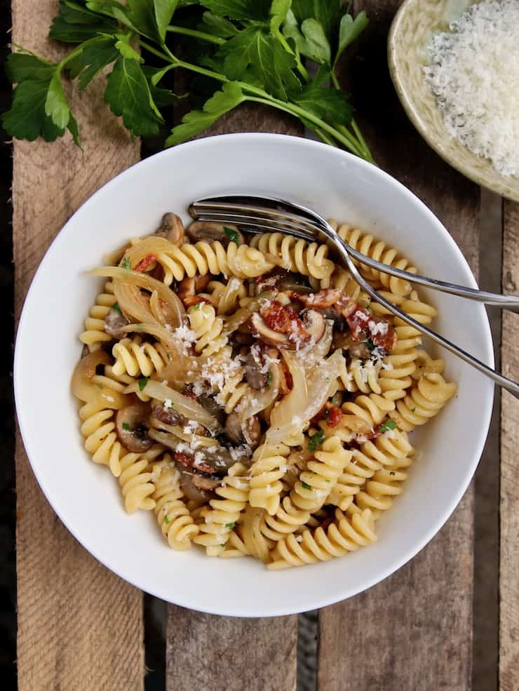 Pasta with Bacon, Onions and Mushrooms, plated in bowl with fork, grated cheese