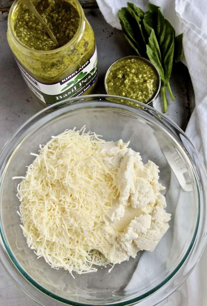 Cheeses in bowl and jar of pesto ingredients.