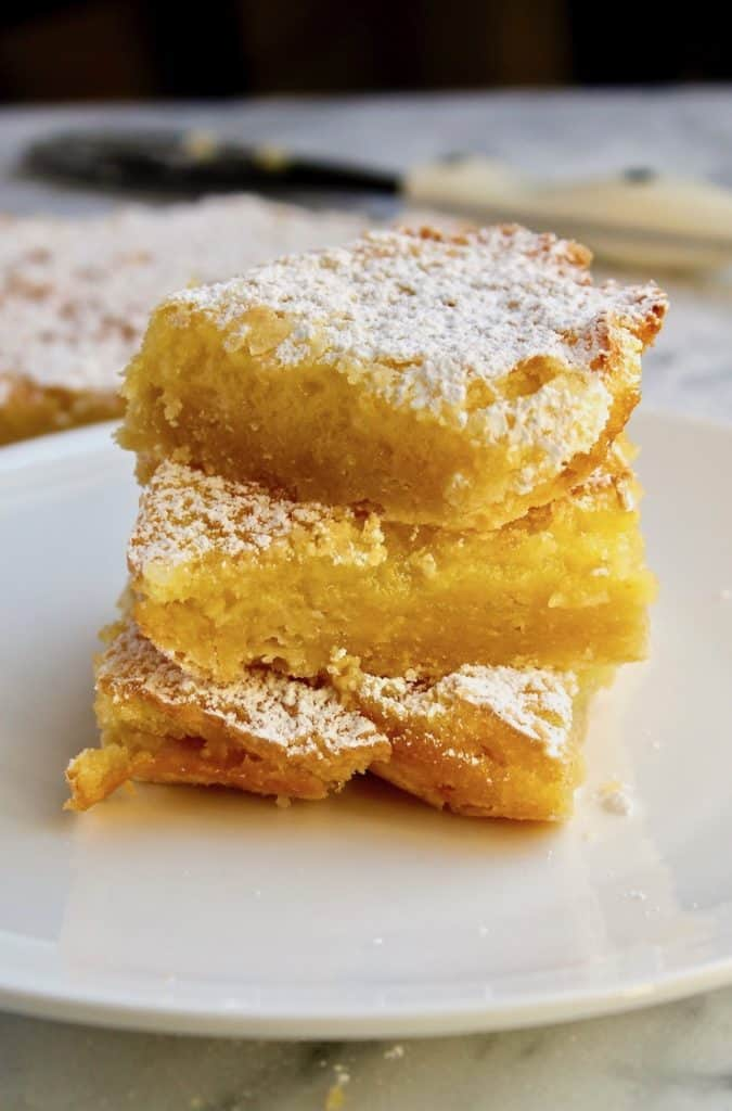 Lemon Squares, three bars stacked on plate.