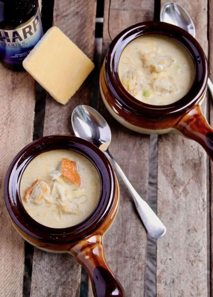 Irish Beer Cheese Soup, in two bowls with croutons and beer and cheese in background.