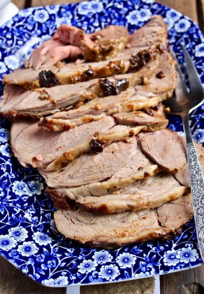 Mustard and Herb Roasted Leg of Lamb, lamb sliced on serving platter.