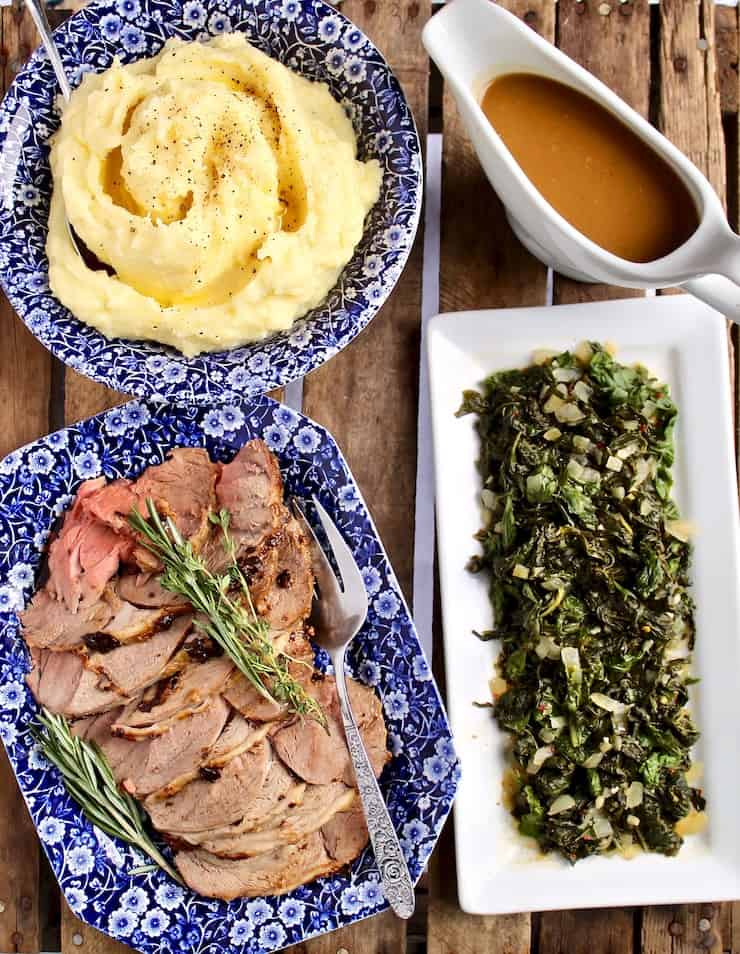 Easter dinner, lamb sliced on platter, mashed potatoes, gravy and braised greens.