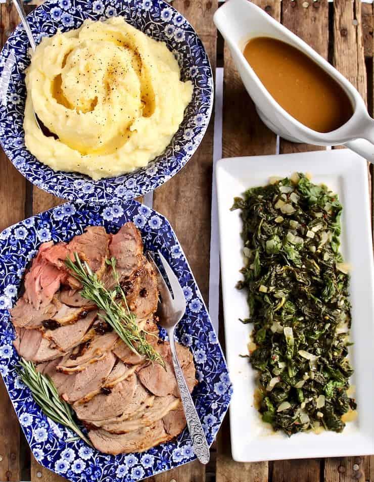 Easter dinner, lamb sliced on platter, mashed potatoes, gravy and braised greens.