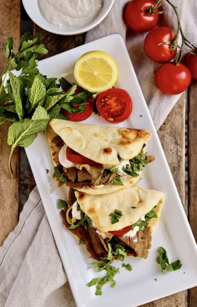 Leftover Lamb Flatbreads, on serving platter with tomatoes, lemon and fresh herbs.